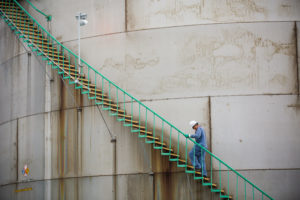 man in blue uniform walks up stairs to water tank