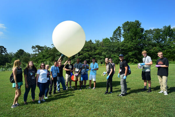 Students play outside will large helium balloon