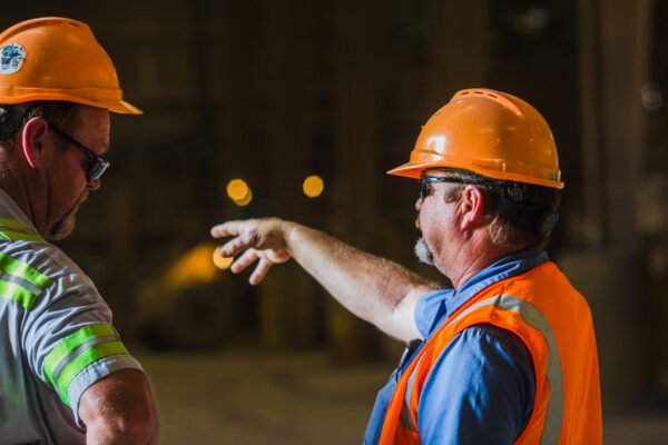 Two men wearing orange hard hats working in a construction setting