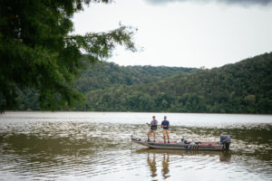 Two men stand in boat with fishing poles surrounded by mountains