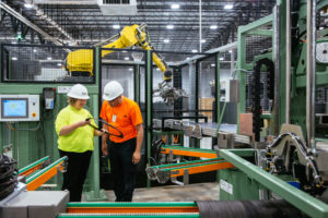 Man and woman inspect plastic ring in manufacturing setting