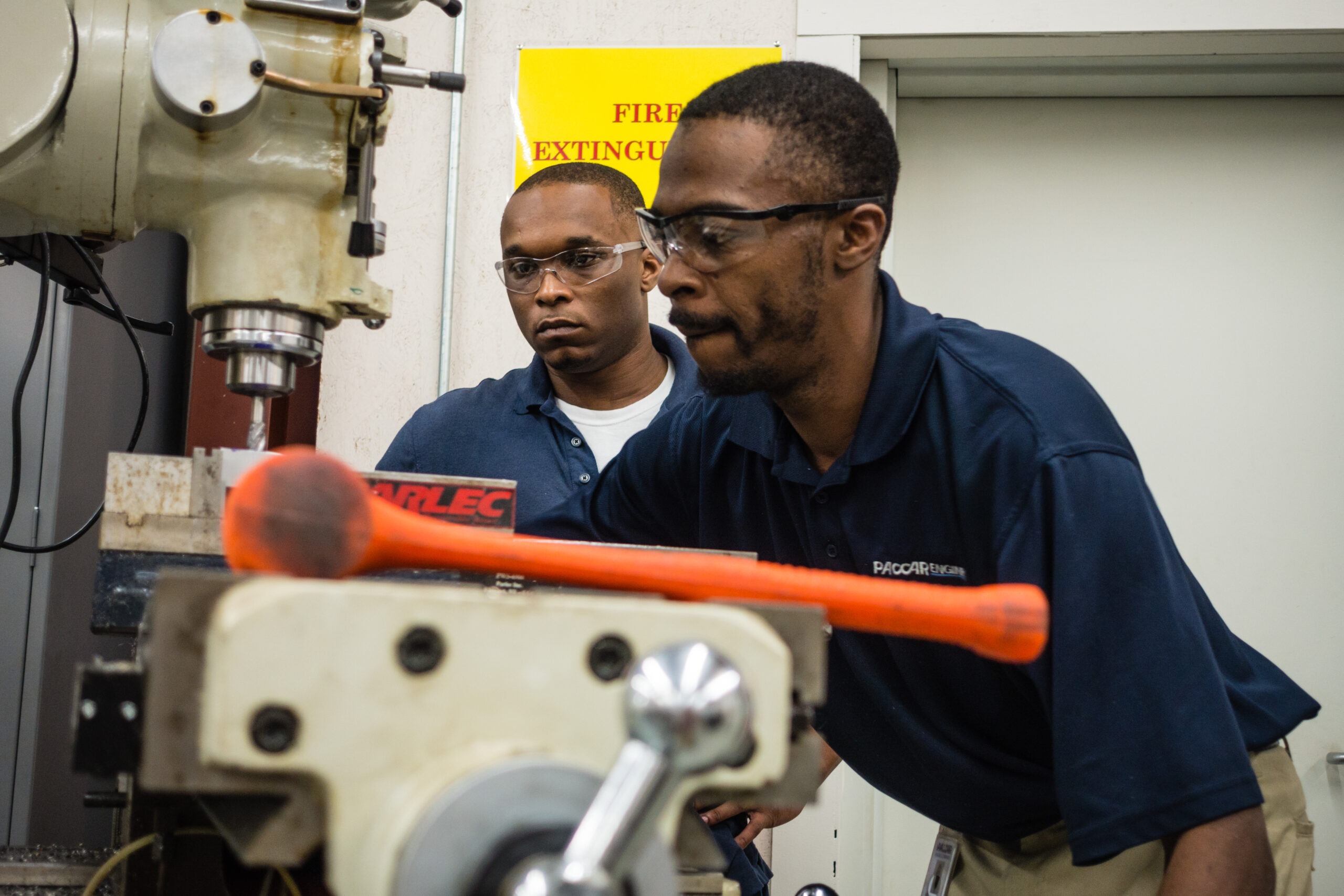 2 men in blue polos working in an industrial setting