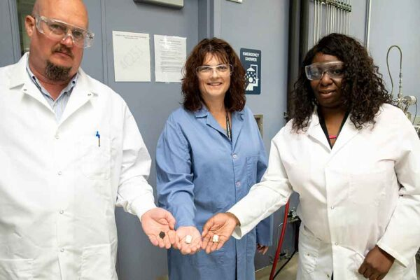 Three scientists show off work in research lab