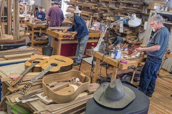 Men work on building guitars