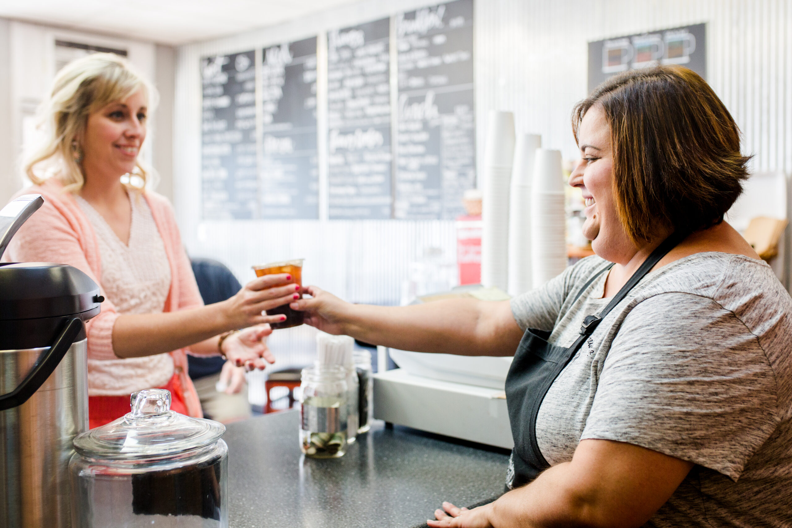 Cashier at coffee shop hands iced coffee to customer