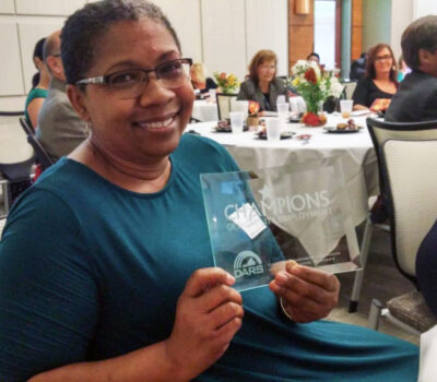 Community Recovery Program's Program Manager Lisa Smith with the Champions award for community collaboration.